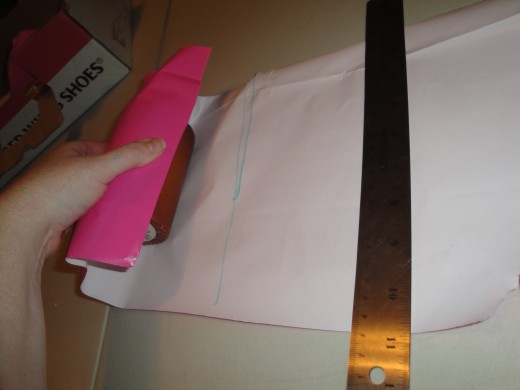 "Making sure your item is straight in the paper, roll the paper over, and mark where the paper meets, plus 1"".  Then cut along mark, fold edge over slightly with firm crease then tape into place."