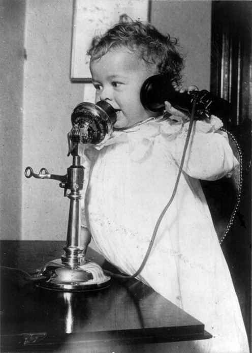 A Little Baby Using an Early Telephone