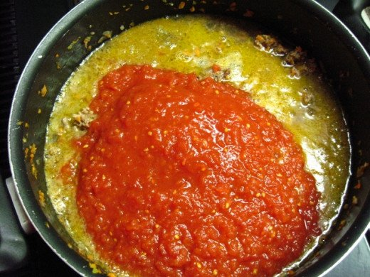 Add the pureed whole tomatoes and  including their can juice.
