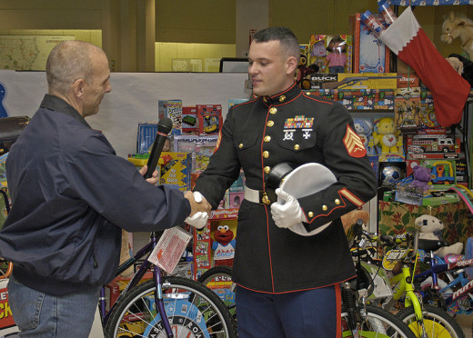Baton Rouge, LA, 12-10-05 -- Hurricane Katrina FEMA Federal Coordinating Officer Scott Wells turns over donated toys to Marine Corps Sgt. Geberth. The Baton Rouge JFO Toys for Tots drive netted donations that filled 2-26 foot Penske box trucks which