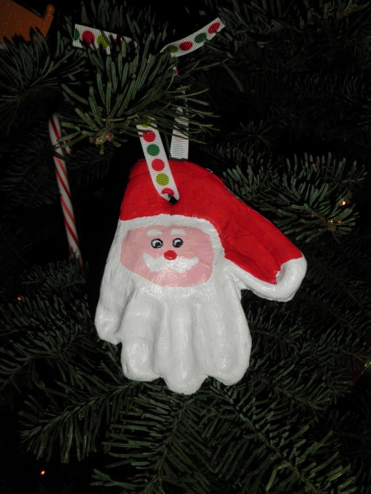 A Santa ornament made from a childs hand-print, made from a salt dough clay recipe.