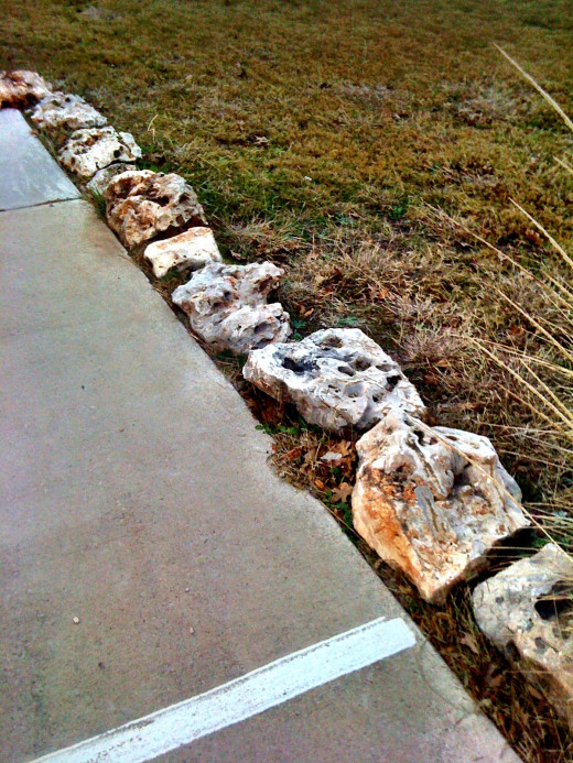 Stones line a green area along a parking lot keeping cars off the grass!
