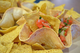 Place several tortilla bowls with dips on a platter and surround with dipping chips.