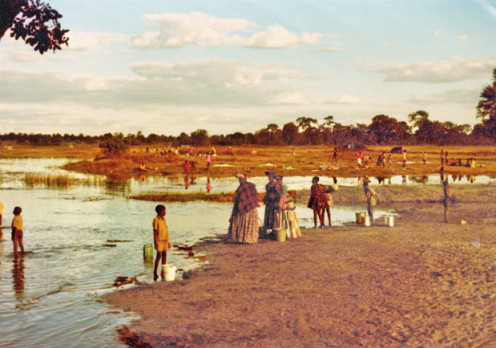 Women and children in Botswana wash clothes, bodies, and gather water from the Thamalakane River (1975).