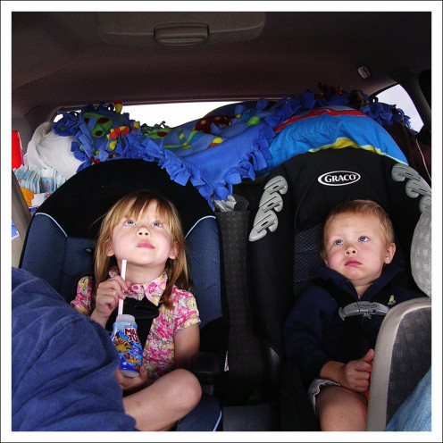 While a challenging scenario to travel with two in diapers, it can be done!  These two are watching a video on the vehicle's DVD player. They are kept satisfied with drinks and toys (behind them).  Mom and Dad prepared correctly for this road trip!