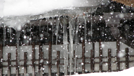 Icicle and falling snow, fast shutter speed results in dots of snow.