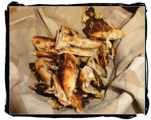Naan, toasted and cut up and served in a cloth lined bowl.