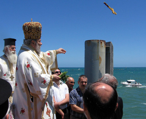 Greek Orthodox Bishop performs Great Blessing of Waters on Theophany, releasing the cross off the Glenelg Jetty, South Australia, for one of the swimmers to bring back.
