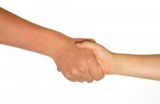 Demonstrate the proper hand shaking technique to kids as part of a good manners lesson.
