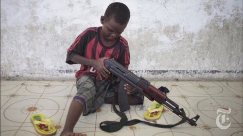 A child in Somalia plays with his toy that gives him his seeming identity and voice: an AK-47