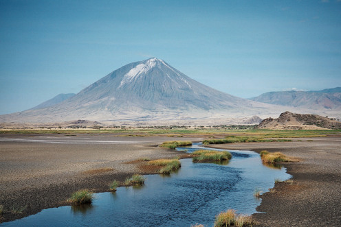 This is Lake Natron, which contains natron that includes baking soda and salts, in Tanzania. Mt. Lengai is in the background.