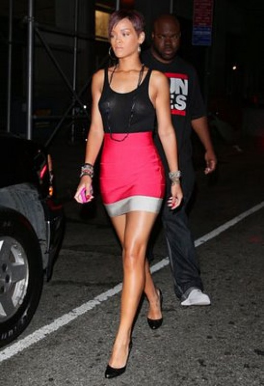 Rihanna showes great style pairing short high waisted skirt with tank top, and adding high heels and long necklace.