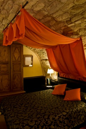 An ethnic themed bedroom with stone wall/ceiling and brightly coloured bed canopy draped in tribal fashion.