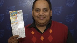 Khan happily displays his winning ticket