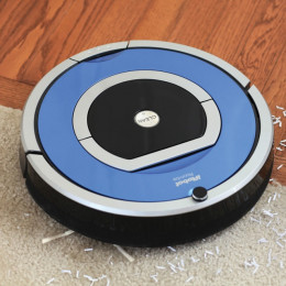A Roomba iRobot automatic vacuum that cleans all surfaces from carpet to laminate to tile by gliding across surfaces picking up dirt along the way.