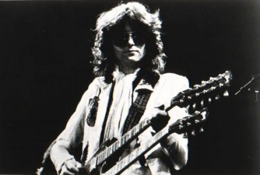 A promotional black and white image of Jimmy Page, performing with the rock group Led Zeppelin in 1977, officially issued by Swan Song Records.