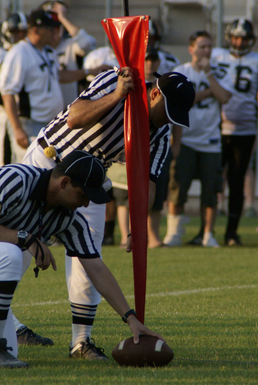 Referees measuring for a first down without the benefit of the yellow line