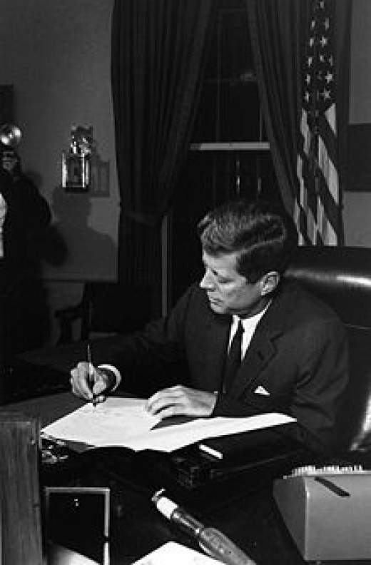 President Kennedy in the Oval Office on October 23, 1962, signing a proclamation for the blockade of the delivery of offensive weapons to Cuba