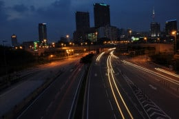 Light trails with a city skyline in the background
