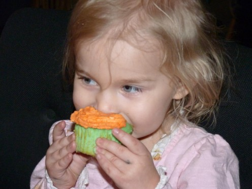 The birthday girl with her green and orange cupcake.