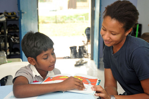 Operations Specialist 2nd Class Janis Jackson tutoring a student in reading English in Kuala Lumpur, Malaysia