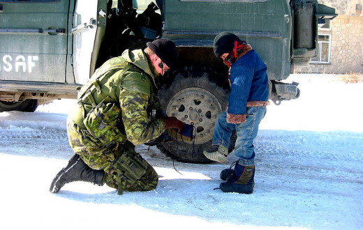 TKnoxB photographed an International Security Assistance Force (ISAF) soldier on January 31, 2005 helping an Afghan child with his boot. The ISAF—Coalition Force—is a NATO-led security mission in Afghanistan.