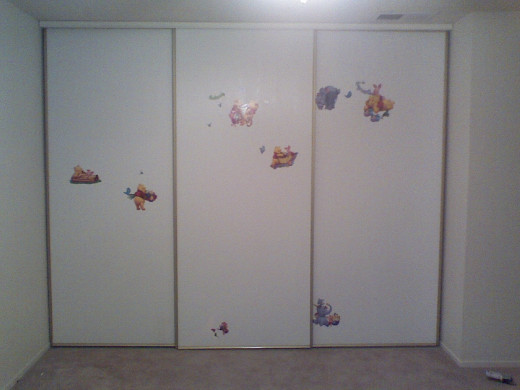 Closet covered in stickers hiding holes.
