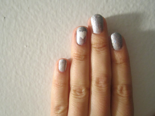 Silver nails with glitter polish and a white heart on the ring finger.