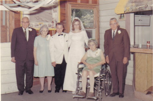 "Sandy and Andy w/ Grandparents. The woman in the wheelchair is Wreatha Mae Elwood, and beside her is Cyril M. Elwood. We called them ""Mommoms and Papaws""."