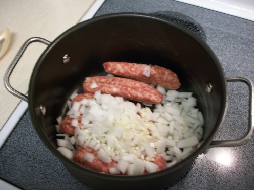 Step 3.  Remove casings from sausage. Dice the onion, mince the garlic, sliver the carrots. Cook sausage, onion, garlic, and slivered carrots over medium heat until sausage is browned. Stir to crumble.