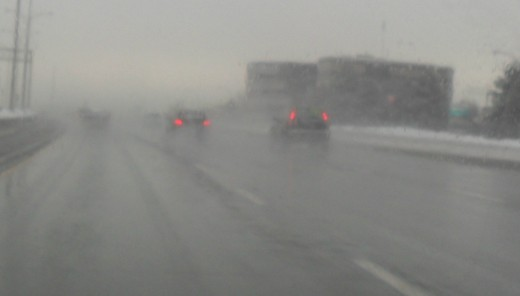 Winter Driving Safety: Always turn your lights on when driving in extreme weather. There are several cars in this picture without their lights on, reducing their visibility to other drivers.