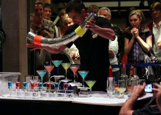 A talented bartender shows off flair for the crowd by pouring 8 martinis at the same time.