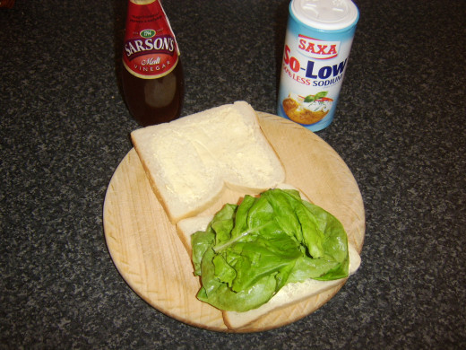 Lettuce is laid on bread and seasoned with salt and malt vinegar