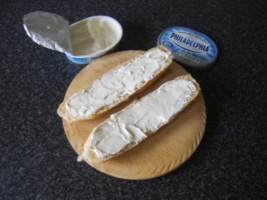 Cream cheese is spread on both halves of the sub roll