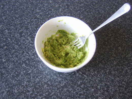 A fork is used to mash the avocado with salt and pepper