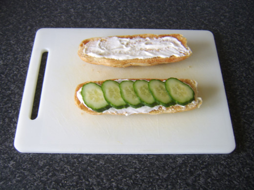 Cucumber slices are laid on top of the mayo on the bottom half of the sub