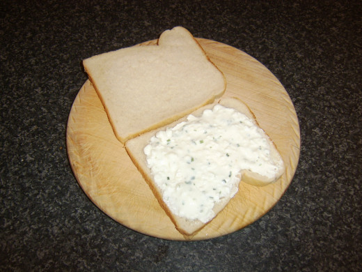 Cottage cheese is spread on one slice of bread