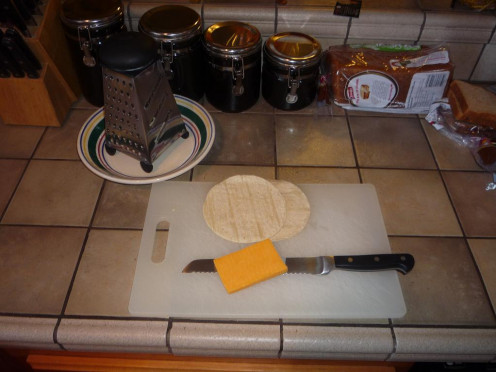 You'll need just a few things: some small tortillas (two per quesadilla), some cheese, and a cheese grater.  Don't forget a pan and spatula for cooking.