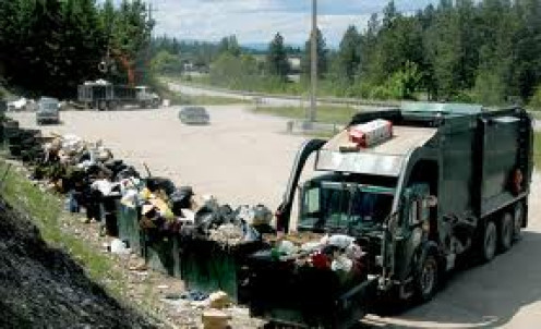 Garbage dumpsters filled up and being picked up by a garbage collection truck.