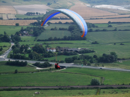 Paraglider off Mount Caburn The busy A27 between Beddingham and Lewes far below on a warm summer day