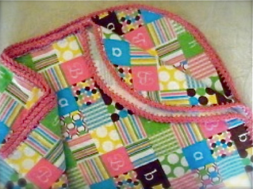 A wow-pink crochet edging highlights the bright colors of this flannel blanket.