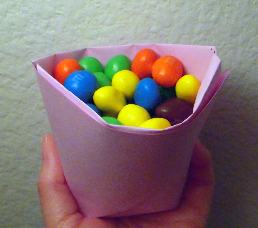 "A paper cup folded from a piece of paper 8.5""x8.5"" will hold approximately 53 peanut M&Ms. This cup cannot stand up by itself."