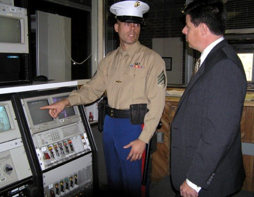 A Marine Security Guard reviews the embassy's security alarm system with the regional security officer.