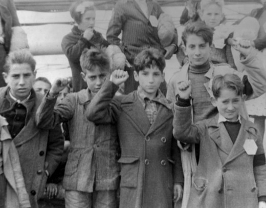 Republican children preparing to be evacuated in the aftermath of defeat to the Nationalists. Here, they are giving the Republican salute- a sign of defiance.