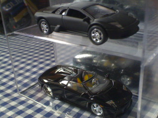 The one of the top is Bruce Wayne's Lambo (The Dark Knight) that saved the life of the snitch while the one on the bottom appeared on the first film of Christian Bale as Batman