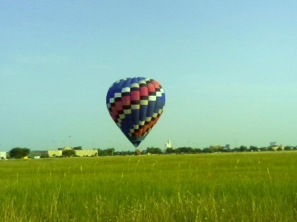 The hot air balloon hovered ABOVE the ground.