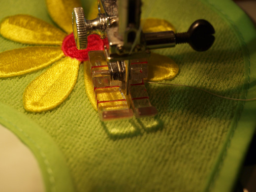 Sewing the applique onto the bib