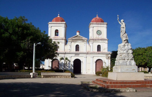 Uvegna photographed San Fulgencio's Parish Church and the Statue of Liberty in Calixto Garcia Park in Gibara, Holguín Province, Cuba on  February 13, 2009.