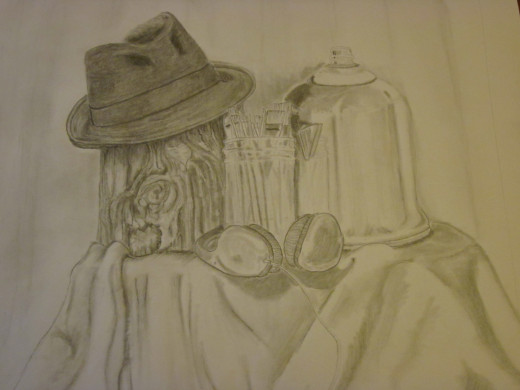 For the self portrait still life, you gather some of your possessions, arrange and draw. Here I have a coffee pot, a mason jar full of paint brushes, headphones, a stump (to represent my love of nature) and an old fedora.