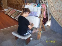 A lady weaving a kilim outside a shop in the bazaar.